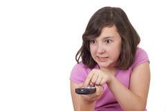 有电视的美丽的十几岁的女孩遥控在她的手上 免版税库存图片