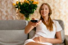 有电视遥控的妇女在手中看电视的,当在家时坐沙发 库存照片