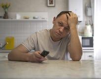 有电视遥控的年轻可爱的人在厨房里坐 免版税库存照片