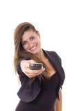 有电视遥控的微笑的女商人 免版税图库摄影
