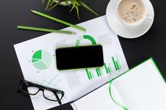 有电话、图和咖啡的办公桌 免版税库存图片