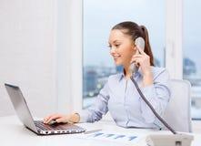 有电话、膝上型计算机和文件的女实业家 免版税库存图片