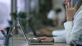 有电话中心的雇员与客户的电话交谈,研究膝上型计算机 免版税图库摄影