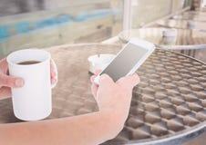 有电话和咖啡的手在大阳台 图库摄影