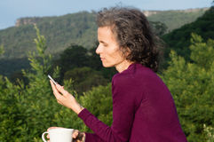 有电话和杯子的成熟妇女在风景 免版税图库摄影