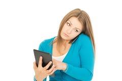 有电话和片剂的美丽的妇女 免版税库存照片