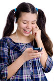 有电话和耳机的愉快的女孩 免版税图库摄影