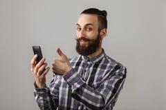 有电话展示赞许的有胡子的英俊的人在被摆正的蓝色 库存图片