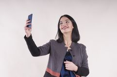 有电话微笑的括号演播室的年轻美丽的女实业家,做selfie 库存照片