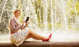 有电话的一名令人愉快的妇女 免版税库存照片