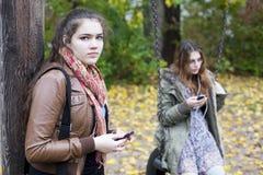 有电话的两个女孩 库存图片