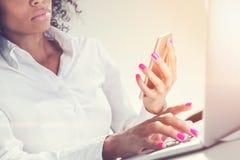 有电话的严肃的非裔美国人的妇女 免版税库存照片