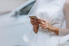 有电话的典雅的新娘在手上 免版税库存照片