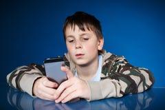 有电话的十几岁的男孩在手中 图库摄影