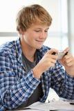 有电话的十几岁的男孩在类 免版税库存图片