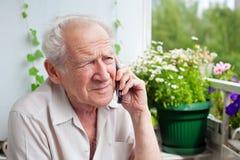 有电话的哀伤的老人 库存图片