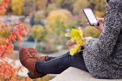 有电话的女孩在她的手上坐小山,黄色叶子 Aut 免版税图库摄影
