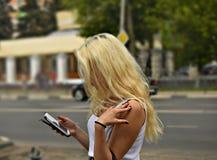 有电话的女孩在手中总是网上在城市 免版税库存照片