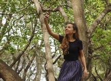 有电话的女孩在寻找连接的森林里 免版税库存图片