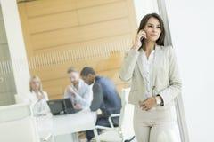 有电话的女实业家在办公室 免版税库存图片