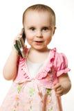 有电话的小女孩在一件桃红色礼服 库存照片