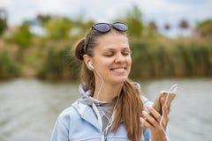有电话的年轻微笑的妇女听到在耳机的音乐有接近的眼睛的 免版税库存照片