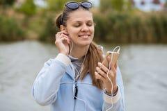 有电话的年轻微笑的妇女听到音乐 免版税库存图片