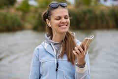 有电话的年轻微笑的妇女听到音乐 免版税库存照片