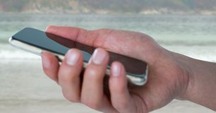有电话的手反对模糊的海滩 免版税库存图片