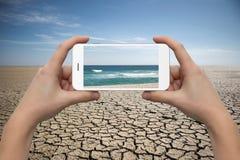 有电话的手在沙漠背景 库存图片