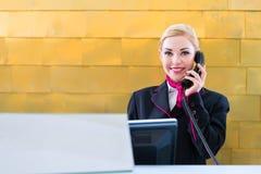 有电话的接待员在服务台上在旅馆里 库存图片
