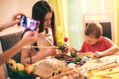 有电话的母亲拍摄孩子的,当他们绘复活节彩蛋时 库存照片