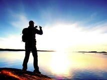有电话的游人在手中和在岩石的背包立场 看在蓝色海的远足者 免版税库存图片