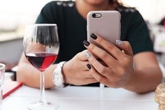 有电话的美丽的女孩在有gla的餐馆递坐 免版税图库摄影