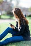 有电话的美丽的微笑的妇女坐一棵草本质上 库存图片