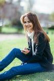 有电话的美丽的微笑的妇女坐一棵草本质上 免版税库存图片