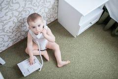 有电话的逗人喜爱的男婴 免版税图库摄影