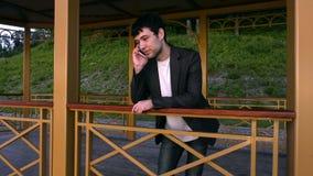 有电话的年轻人在手中在眺望台 股票录像