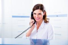 有电话的医生护士在服务台 免版税库存图片