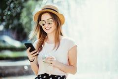 有电话chating的年轻秀丽在互联网饮料mojito水果鸡尾酒的妇女或海浪反对在街道的喷泉 免版税库存图片