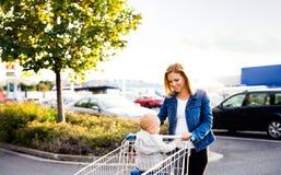 有男婴去的购物的母亲在停车场 免版税库存图片