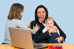 有男婴和一个小女孩的工作母亲 免版税库存照片