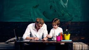 有男孩图画的老师在学校课程的学校书桌坐绿色校务委员会背景  概念了解 股票视频