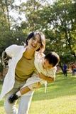 有男孩的乐趣草坪母亲 库存图片