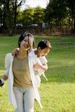 有男孩的乐趣草坪母亲 免版税库存图片