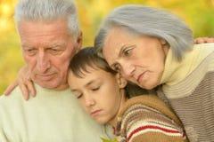 有男孩的哀伤的祖父母在公园 免版税库存图片