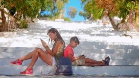 有男孩的少妇坐看智能手机的台阶 影视素材
