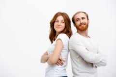 有男孩的快乐的红头发人女孩在白色衬衣身分穿戴了 免版税库存图片