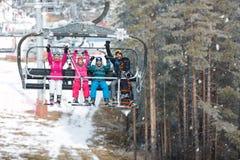 有男性和女孩的父母升降椅的在滑雪爬上 免版税库存图片