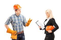 有男性的体力工人与女性建筑师的一次交谈 库存照片